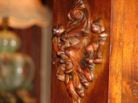 carved wooden face with beard on side of wooden furniture, side-angle view