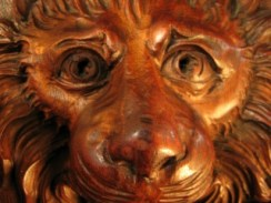 wooden carving of a lion's face