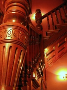 side view of wooden banister and stairs with detailed carvings