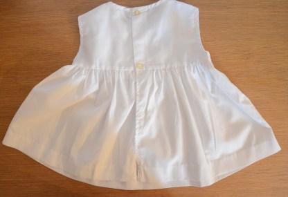 Robe blanche smockée rose pour enfant, taille 12 mois en Tergal. Fabriquée avant 1981 par la société Rhodiaceta.