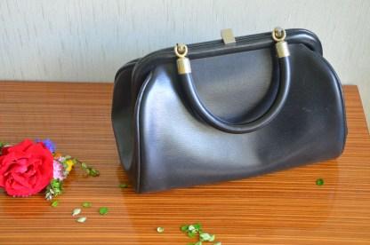 Sac à main vintage en cuir noir, intérieur en tissu rayé couleur marine avec une petite poche à l'intérieur qui se ferme par une fermeture éclair. Le sac est rigide et ne possède qu'une anse.