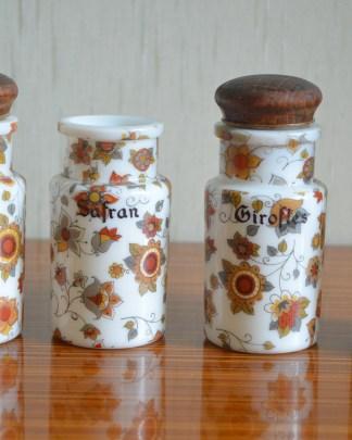 Lot de 4 pots à épices (muscade, safran, girofle, épices) en opaline et bois. Il manque un bouchon et l'un des pot est ébréché. D'un côté le mot est en français et de l'autre côté il est écrit en italien.