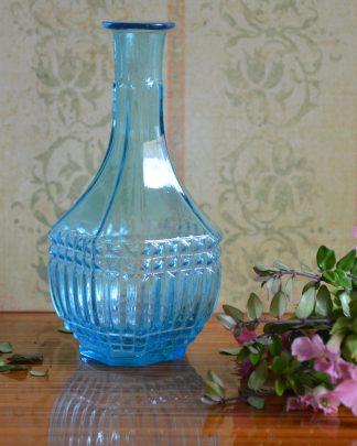 Soliflore en verre bleu au col évasé et ventre bombé.