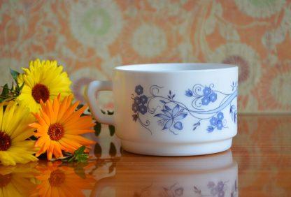 Tasse de grande capacité, de la marque Arcopal et de la collection Aster au décor de fleurs et d'oignons bleus.