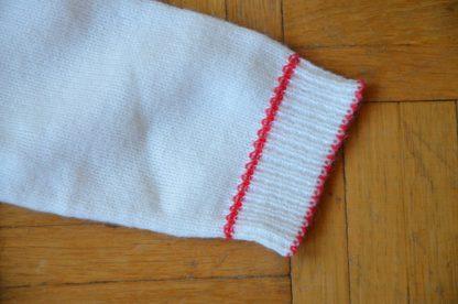 Robe d'hiver en tricot pour enfant, couleur blanc et bordure rouge. Se ferme pas un petit bouton au niveau de l'épaule.
