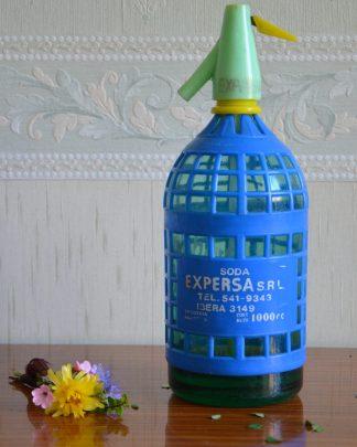 Siphon de limonade. Soda expersa srl, industria argentina. Cont neto: 1000cc. Tel: 541-9343. Ibera 3149. La bouteille est en verre et le revêtement est en plastique. Le système de siphon n'est plus utilisable, cet objet est seulement décoratif. Le siphon fait 1.669 kg pour 30.5 cm de haut et 8.5 cm de diamètre.