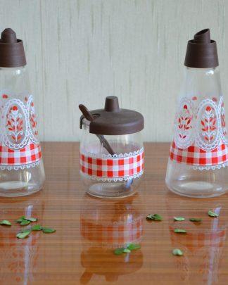Lot de condiments de table vinaigre/huile et moutarde en verre, VMC France, Reims. Motif Vichy rouge, dentelé et fleurs rouge. Le pot à moutarde fait 12 cl. Il fait 8 cm de haut et 5 cm de large. Les contenants huile et vinaigre font 15.5 cm de haut et 6 cm de large.