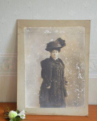 Photo en noir et blanc collée sur un carton. Représente une femme avec un chapeau et en manteau de fourrure, fin du 19ème siècle.