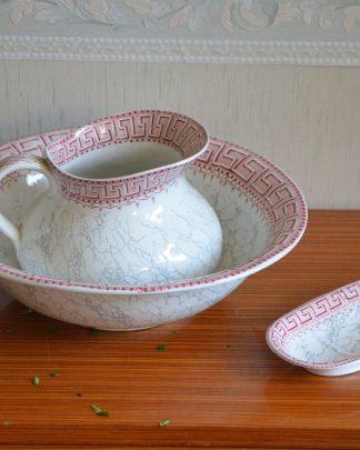 LUNEVILLE, Keller & Guérin - Nécessaire de toilette en faïence fine modèle Athènes à décor de frises de grecques roses sur fond marbré. Il comprend : un broc, un bassin, un porte-savon.