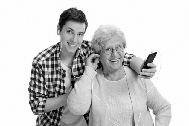 Mature woman listening to music on phone with her grandson
