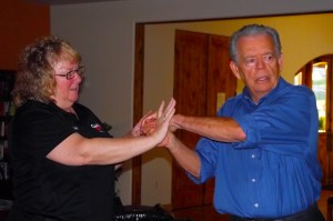 Using Jan Sullivan as a would-be attacker, John Hughes demonstrates how easily fingers can be broken and how effective this would be to ward off an attack when someone grabs you from behind.