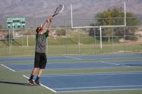 Tyler Hughes Bulldog top seed serving against a Roadrunner opponent Monday afternoon. Photo by Lou Martin.