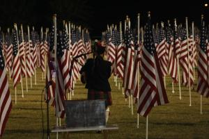 Bagpiper Dennis Hangey plays patriotic selections as he disappears into the One Thousand Flag display Tuesday evening. Photo by Lou Martin.