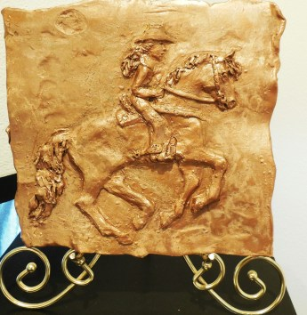 Tammy Symons created a horse and rider in bas relief sculpture, inspired by her own poem about competitive barrel racing.