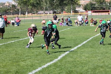 Mason Montoya (7) Running for a touch down. Photo by Stephanie Montoya.