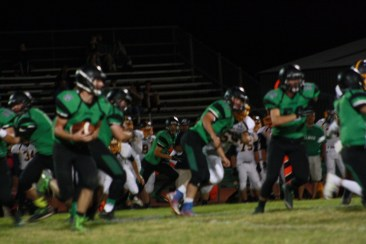 Bulldog running back Kai Mitchell, stepping in at quarterback, follows a bevy of blockers for 50 yards and a Bulldog T.D. to begin Friday's rout of Boulder City. Photo by Lou Martin