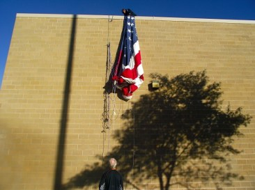 Volunteers haul the large flag up the side of the Mesquite Recreation Center.  The flag will continue to adorn the wall for the entire week as part of the 1000 Flags over Mesquite. Sponsored by the Exchange Club of Mesquite, 1000 Flags are flying for the tenth year in Mesquite honoring veterans past and present. Photo by Teri Nehrenz.