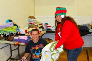 Mesquite resident Gina Benell carefully chooses the toys she thinks will make her children smile the brightest on Christmas morning during the distribution of the Toys for Tots drive which was held on Dec. 18 at the old Boxing Club.   Elf helper, Roberta Franco, shows Benell a very nice hand-made and donated afghan which might be just perfect for any little girl's room.  Photo by Teri Nehrenz.