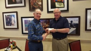George Gault, Mesquite Regional Business Inc. CEO, left, accepts a $2,000 investment from Steve Arbour who represents American Bank of the North on Wednesday, March 9.
