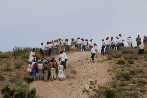 In a reenactment of church lore, angels in white descend from the top of Angel's Hill to help pull handcarts to the top of the steepest slope during a four-day desert trek through the mountains south of Bunkerville and Mesquite. Photo by Barbara Ellestad.