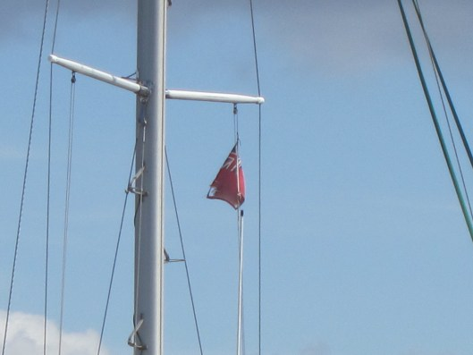 A Red Ensign courtesy flag declares that a boat is British, but civilian rather than military. This is the kind of flag Chris and John fly on Sara II.