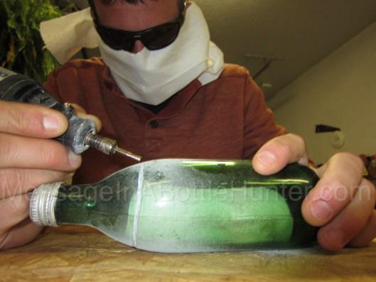 Evan Buffington using Dremel tool to open German message in a bottle, wearing a creepy mask