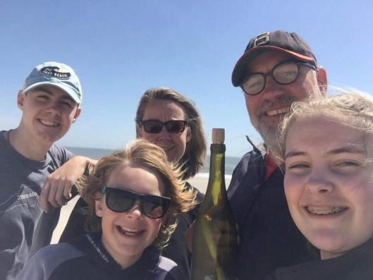 Spalding family with #NolansGift message in a bottle on Bald Head Island, NC, where they found it.