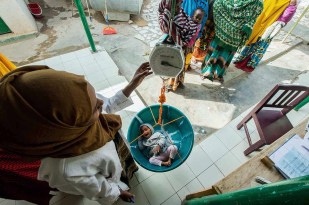 A nutrition worker in the northwest city of Hargeisa weighs a girl called Obah to see if she has gained weight in the past month. (Credit: WFP/Kabir Dhanji)