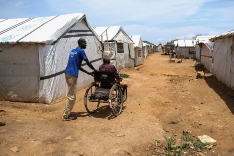 A relative pushes John Biel Dup's wheelchair through the dirt paths of Protection of Civilians Camp 3 in Juba,. The uneven paths make it difficult for people with physical disabilities to move around the camps..