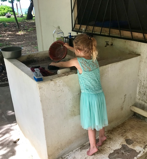 small-girl-washing-dishes-teal-dress