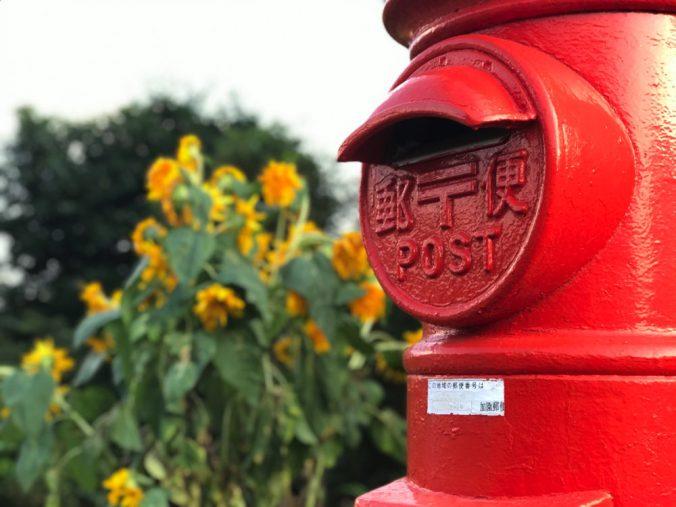 丸型郵便ポストと向日葵