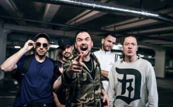Callejon band photo. The band are in an underground car park, the members are wearing casual street clothing like tracksuits, hoodies and thin zip up jackets. Their lead singer points at the camera while the other members stand behind him looking intimidating, but presumably in a joking manner.