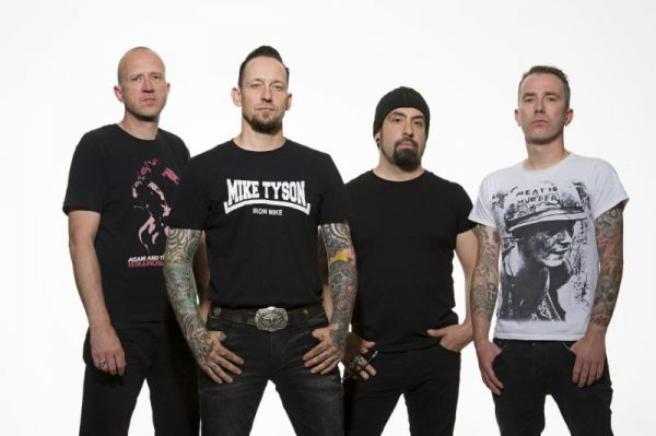 Volbeat band colour photo. The band are casually stood in front of a white wall with their thumbs or hands in their pockets.