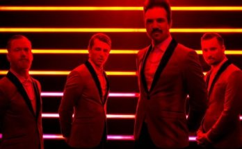 Royal Republic band photo. The band are wearing tuxedos standing in front of horizontal yellow stripes, the whole picture is lit red