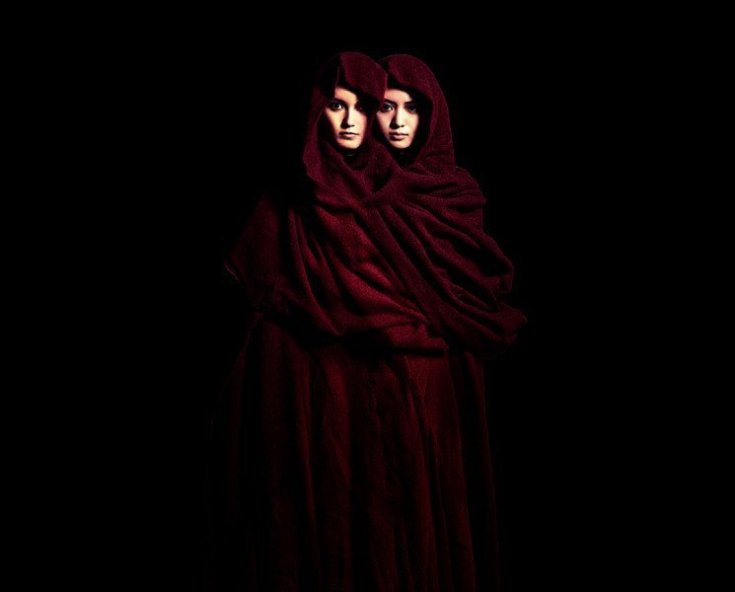Su Metal and Moametal of Babymetal draped in a dark red cloak while the rest of the image is entirely black.