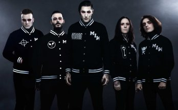 Motionless In White colour Band Photo. The band are all dressed in black American varsity jackets, each of them has dark hair, pale skin and red makeup around their eyes to appear like vampires.
