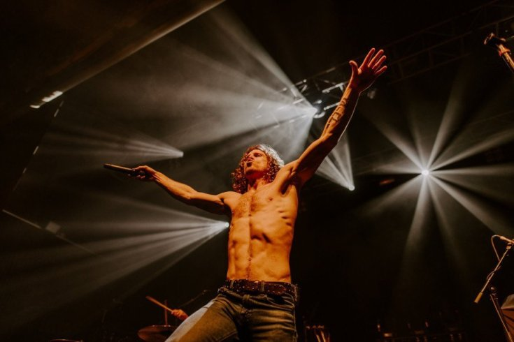 Colour photo of Jonny Hawkins of Nothing More. The background is black with white lights breaking up the darkness with streaks. Jonny stands pursing his lips, topless with his arms outstretched, there's no fat on his body at all. His dark jeans sit low and his muscles are obscured only by his light chest hair and hair on his stomach. His curly red hair hangs down to his shoulders.