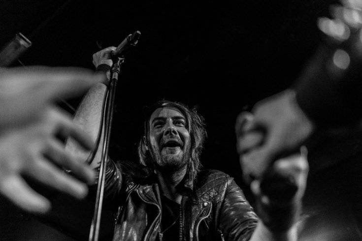 Excited fans reach over photographer Jade Greenbrooke to touch frontman Matt James of The Raven Age in this black and white photo. An amazed looking Matt is in sharp focus shaking hands with one fan while another hand reaches out for him. The hands are out of focus creating a tunnel affect.