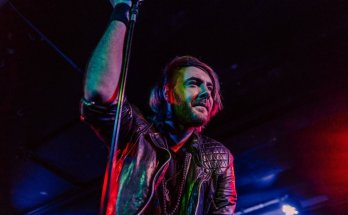 Matt James of The Raven Age looks out at the crowd while leaning on a microphone stand.