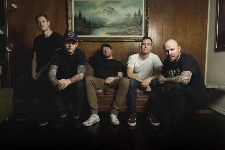 Comeback Kid colour band photo. The band are sitting on a sofa in a small room with a wood panelled wall behind them. On the wall is a painting of a mountain scene. The band are wearing casual clothing - t-shirts, jeans, trainers.