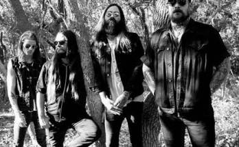 He Is Legend Band Photo, black and white. The band are stood in front of a tree, they are wearing denim jeans and denim jackets with the sleeves cut off