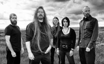 My Dying Bride band photo in black and white. They are stood in a bleak landscape like a large empty field looking website.