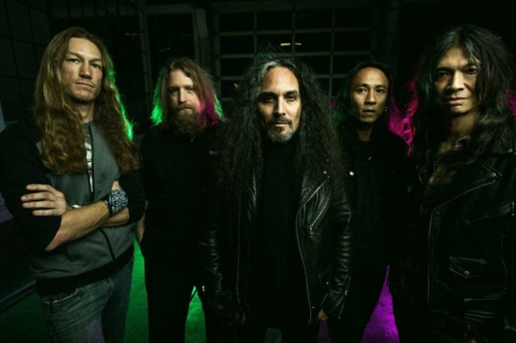 Colour band photo of Death Angel. The band are stood in a dark room backlit with green and purple lights. They all look naturally posed, calm, not relaxed nor threatening. Four of the band members are dressed all in black, two in hoodies, two in black leather jackets. The fifth member wears blue jeans and a grey top. All of them have long hair, some of them sport goatees.