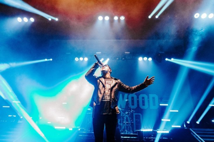 Daniel Murillo of Hollywood Undead sings with his head held back and his left arm outstretched. Behind him the backdrop is flooded with blue light. The picture almost feels religious.