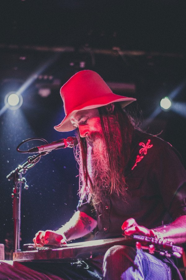 Colour photo of Jonny Halifax sitting with a slide guitar on his lap with a microphone in front of him. He's wearing blue jeans, a black shirt and a red wide brimmed floppy hat. He is looking down at the guitar with his long hair falling slightly forwards past his long beard