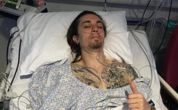 Photo of The Fallen States guitarist Dan Oke in a hospital bed with oxygen tubes in his nose giving a thumbs up sign.