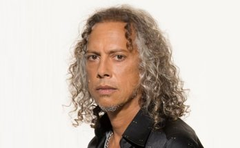 Colour photograph of Metallica's Kirk Hammett. Kirk is wearing a black shirt, and is standing side on to a white wall, with his head turned to face the camera. he is tanned with his dark and grey curly hair falling to his shoulders.