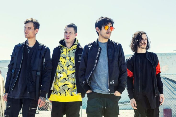 Crown The Empire colour photo. The band are standing together in front of a chain link fence, each of them wearing a light jacket. The picture is bright and the most foremost person in the shot is wearing sunglasses.