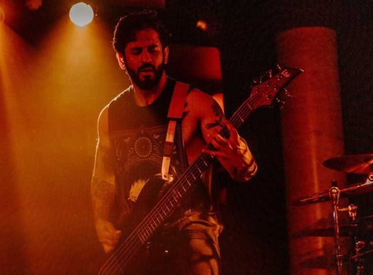 "Photo of Vishal ""V"" Khetia of Heart of a Coward. He is playing bass while wearing a black tank top which shows his tattooed arms. He has short black hair and a full black beard."