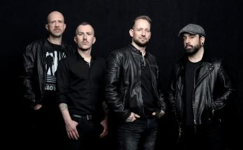 Volbeat band members. Stood in line in front of a black background.